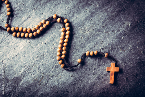 Leinwand Poster Wooden rosary laying on stone background.