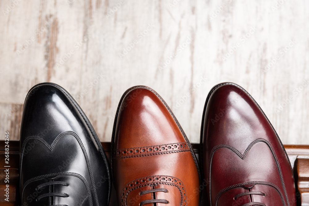 Fototapeta Black and brown full grain leather shoes on wooden display in in men shoes boutique store.