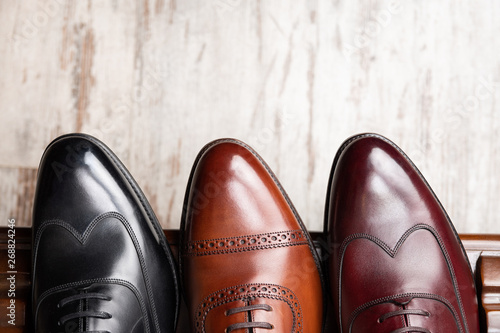 Black and brown full grain leather shoes on wooden display in in men shoes boutique store Wallpaper Mural