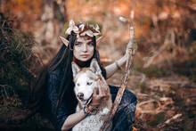 Beautiful Elf Woman Fabulous, Fairy Forest, Famtasy Young Woman With Long Ears, Long Dark Hair Golden Wreath Crown On Head With Red Dog Like Wolf