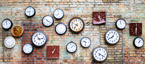 Photo  Collection of vintage clock hanging on an old brick wall