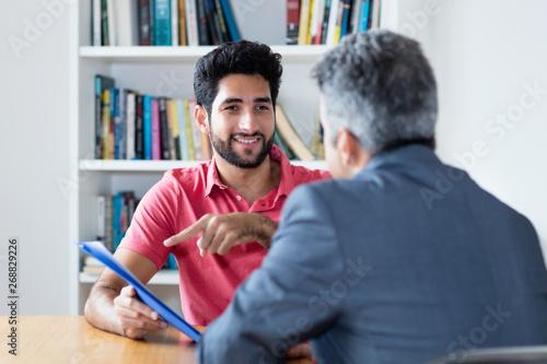 Foto Junger Mann präsentiert sich im Bewerbungsgespräch