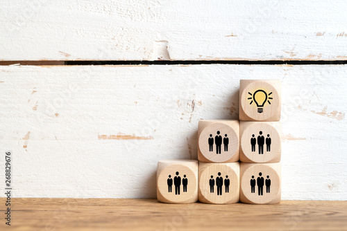 Foto auf Leinwand Texturen many people together having an idea symbolized by icons on cubes on wooden background