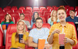 Leinwandbild Motiv cinema, fast food and entertainment concept - smiling red haired teenage girl in checkered shirt eating popcorn from striped bucket over people in movie theater background