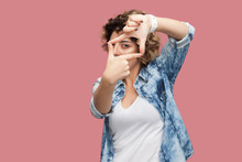 Portrait Of Serious Attentive Young Woman With Curly Hairstyle In Casual Blue Shirt Standing With Crop Hands Composition And Looking At Her Target. Indoor Studio Shot, Isolated On Pink Background.