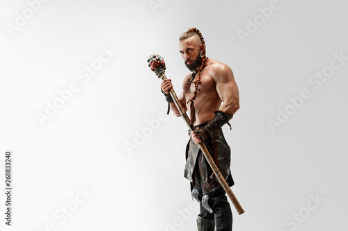 Fototapeta Serious long hair and muscular male model in leather viking's costume with the big mace cosplaying isolated on white studio background. Half-length portrait. Fantasy warrior, antique battle concept. obraz