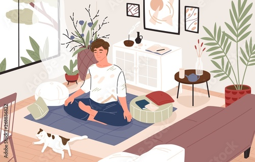 Fotografie, Obraz  Cute guy or boy sitting cross-legged in his room or apartment and practicing yoga