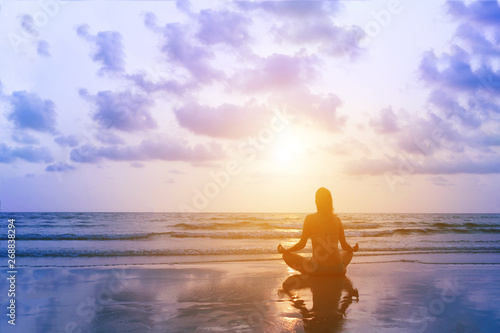 Young woman practice yoga in lotus pose on sunset sea beach in Thailand. Mindfulness and zen. Surreal sky with reflection on sand.