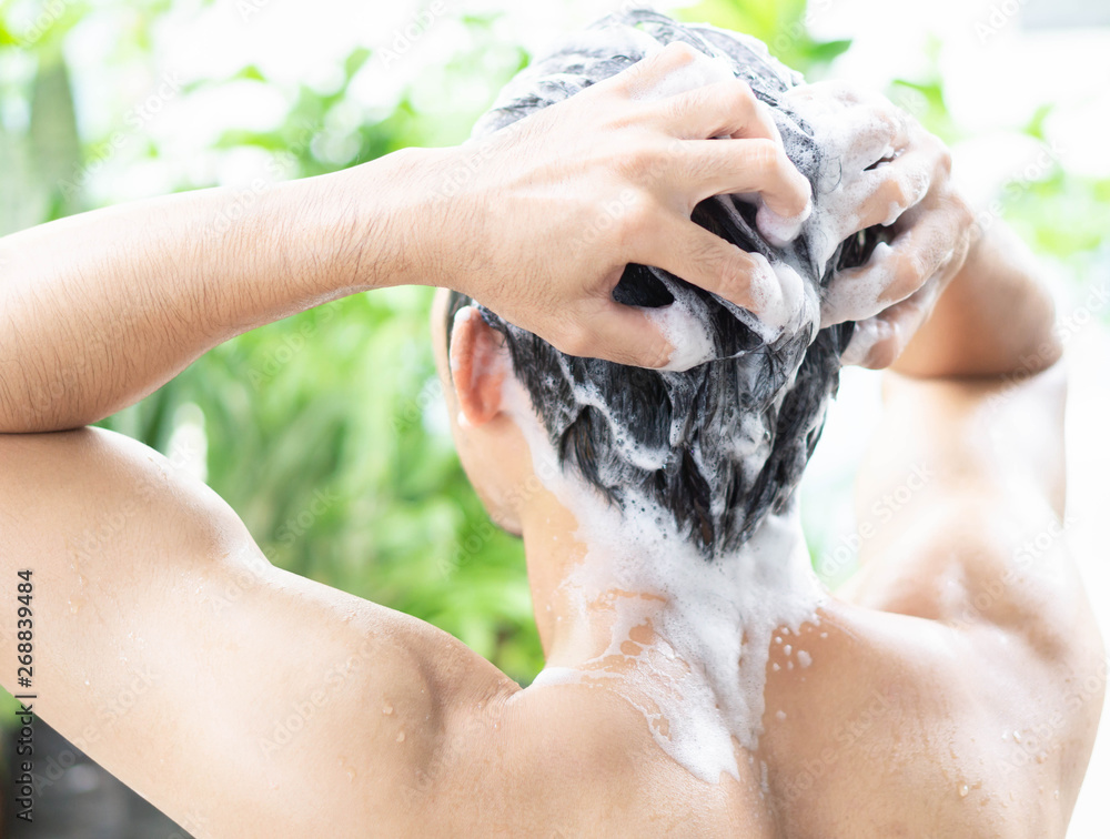 Fototapeta Closeup young man washing hair with shampoo from outdoor, health care concept, selective focus