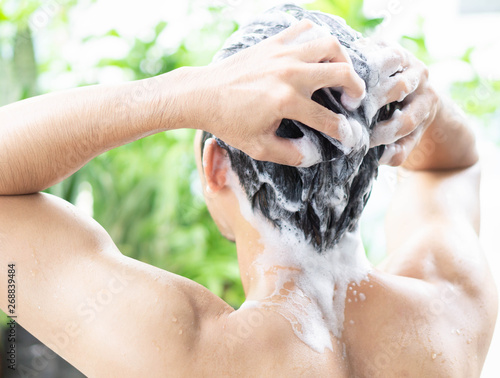 Closeup young man washing hair with shampoo from outdoor, health care concept, selective focus