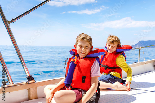 Fototapeta Two little kid boys, best friends enjoying sailing boat trip. Family vacations on ocean or sea on sunny day. Children smiling. Brothers, schoolchilden, siblings having fun on yacht. obraz