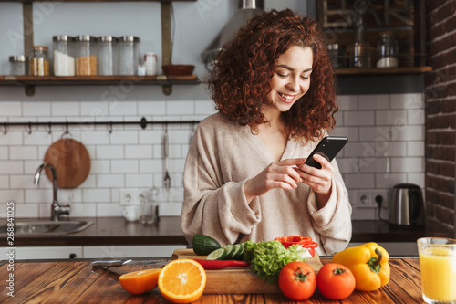 Fototapeta Photo of joyful caucasian woman holding smartphone while cooking salad with fresh vegetables at home obraz