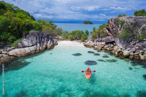 Foto Aerial drone view of man kayaking in crystal clear lagoon sea water during summer day near Koh Kra island in Thailand