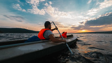 Father And A Son Go Kayaking In The Sunset