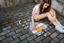 Girl Drawing Colorful Hearth Shape With Chalks