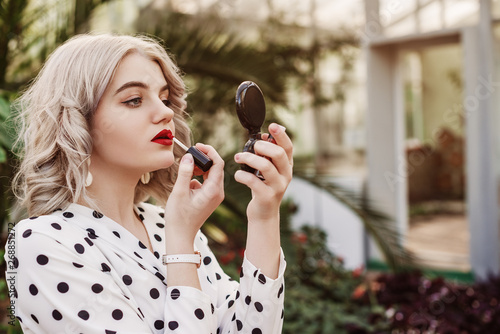 Outdoor close up portrait of young beautiful lady doing make up, using red lipstick, posing in the garden. Copy, empty space for text