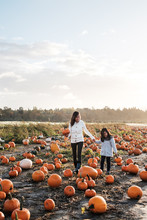 Asian Mother And Daughter Pumpkin Patch During Fall Season