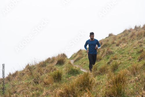 Man cross country running along a track in the mountains.