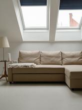 Cozy Beige Couch Under Mansard Windows