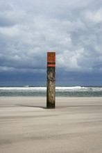 Wooden Pole On The Beach Of Ameland