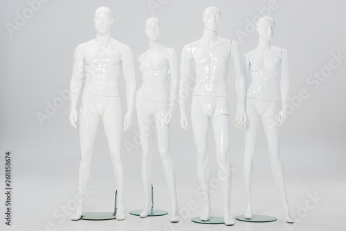 Photo white plastic mannequins in row on grey