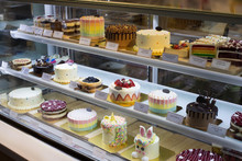 Many Good Looking Design And Colorful Bakery Cake In Refrigerator Windows Show, Present Variety Of Price And Vanilla Chocolate Birthday Cake For Special Occasion, Blur By Frozen Ice Glass