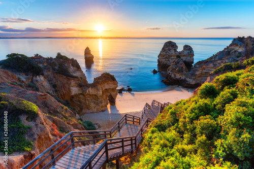 Tuinposter Zonsondergang Camilo Beach (Praia do Camilo) at Algarve, Portugal with turquoise sea in background. Wooden footbridge to beach Praia do Camilo, Portugal. Wonderful view of Camilo Beach in Lagos, Algarve, Portugal.