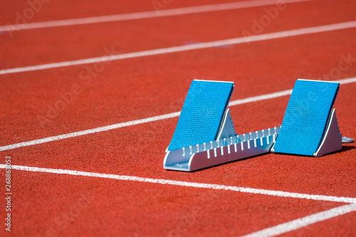 Athletic start block on dark red tartan track Fototapete