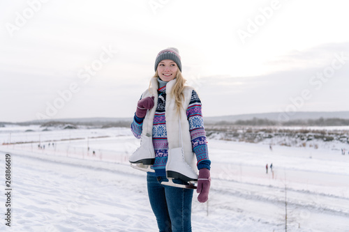 Smiling young woman standing with skates
