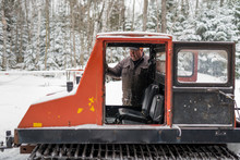 Older Man Steps Into Cab Of Vintage Snow Grooming Machine In Snowy Forest