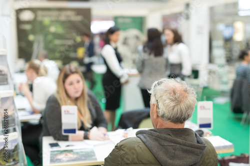 Fotografia  Blured image of client consulting aobout product with saleswoman at business fair