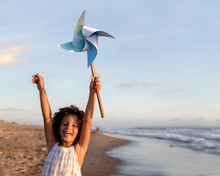 Girl Holding Pinwheel Toy At The Beach