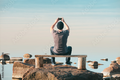 A man sits on a wooden bench and photographs the sea on his mobile phone Fototapeta