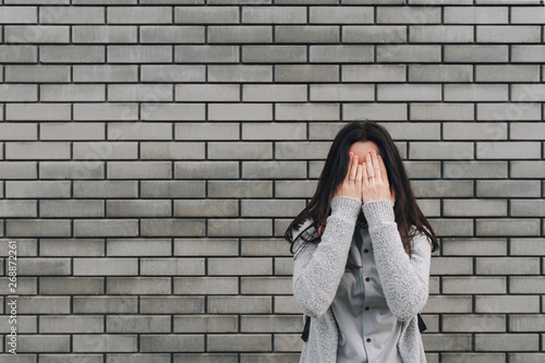 Fotografía  Beautiful young woman on the gray background with sad expression covering her face with hands while crying