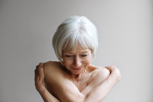 Portrait Of Naked Senior Woman Against Gray Background