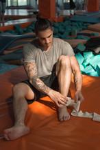 Athlete Wrapping Ancle In Elastic Bandage