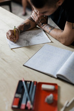 Artist Draws In Sketch Book On Table