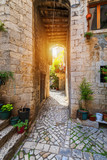 Fototapeta Uliczki - Narrow street in historic town Trogir, Croatia. Travel destination. Narrow old street in Trogir city, Croatia. The alleys of the old town of Trogir are very picturesque and full of charm. Croatia.