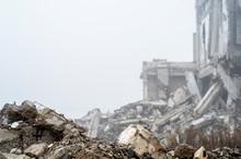 The Remains Of Concrete Fragments Of Gray Stones On The Background Of The Destroyed Building In A Foggy Haze. Copy Space