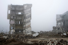 The Remains Of Concrete Fragments Of Gray Stones On The Background Of The Destroyed Building In A Foggy Haze.