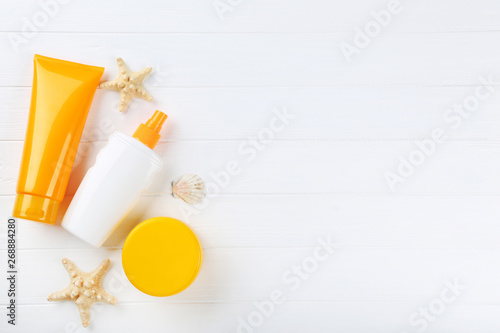 Sunscreen bottles with seashells on white wooden table