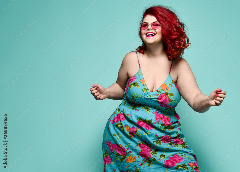 Fototapeta Lucky plus-size lady overweight woman in fashion sunglasses and colorful sundress happy dancing, celebrating