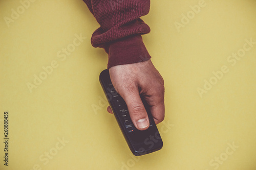 Photo Hand with remote control on a yellow background.