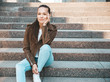 Leinwanddruck Bild - Portrait of beautiful brunette model dressed in summer hipster jacket and jeans clothes. Trendy girl sitting on steps in the street background. Funny and positive woman