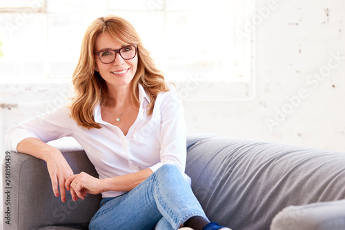 Portrait of attractive middle aged woman relaxing on sofa Canvas Print
