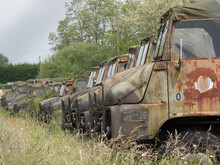 A Line Of Abandoned Rusting World War Two Army Trucks Stand In A Field