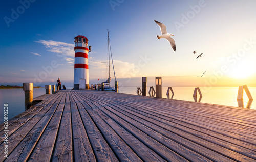 Lighthouse at Lake Neusiedl at sunset near Podersdorf with sea gulls flying around the lighthouse. Burgenland, Austria