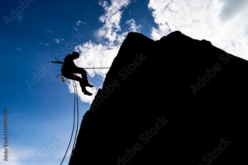A dramatic silhouette of a climber rappeling down a rock wall Canvas Print