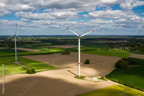Two wind turbines from eye level with shadows on the ground and clouds in the sk Tapéta, Fotótapéta