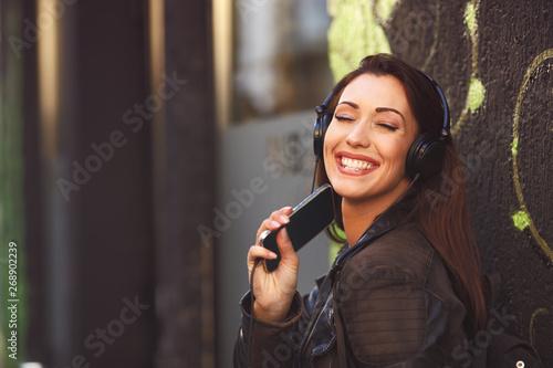 Young woman enjoys music via headphones on the street